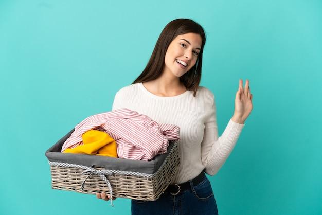 Ragazza brasiliana dell'adolescente che tiene un cestino dei vestiti isolato su fondo blu che saluta con la mano con l'espressione felice