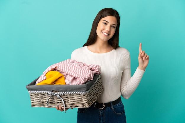 Adolescente ragazza brasiliana che tiene un cesto di vestiti isolato su sfondo blu che mostra e solleva un dito in segno del meglio