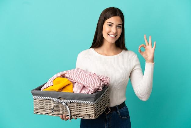 Adolescente ragazza brasiliana che tiene un cesto di vestiti isolato su sfondo blu che mostra segno ok con le dita