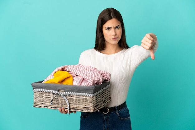 Ragazza brasiliana dell'adolescente che tiene un cestino dei vestiti isolato su fondo blu che mostra pollice giù con espressione negativa with