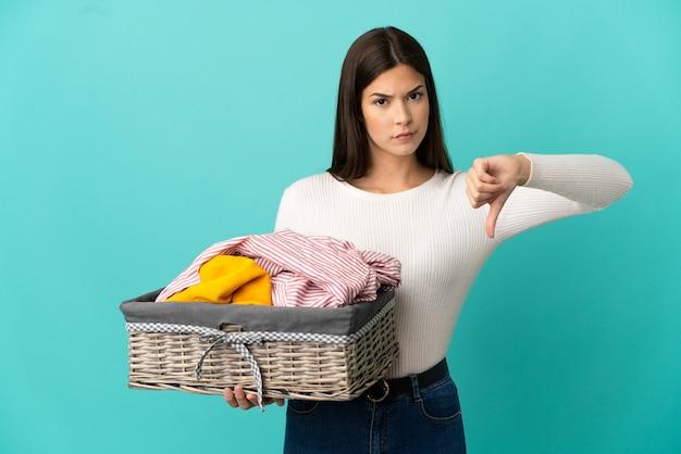 Adolescente ragazza brasiliana che tiene un cesto di vestiti isolato su sfondo blu che mostra il pollice verso il basso con espressione negativa