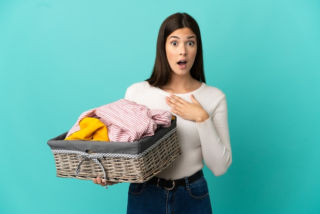 Ragazza brasiliana dell'adolescente che tiene un cestino dei vestiti isolato su priorità bassa blu sorpresa e scioccata mentre guarda a destra