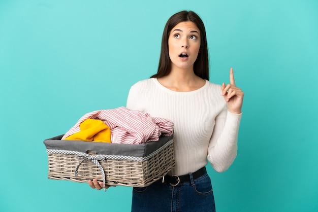 Ragazza brasiliana dell'adolescente che tiene un cestino dei vestiti isolato su priorità bassa blu che pensa un'idea che indica il dito verso l'alto