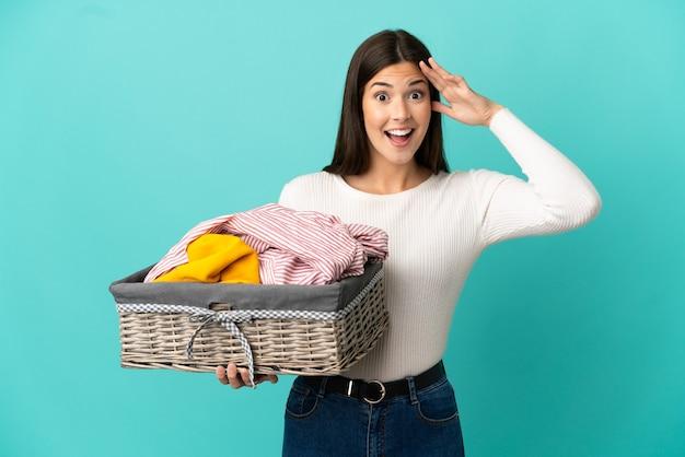 Ragazza brasiliana dell'adolescente che tiene un cestino dei vestiti isolato su priorità bassa blu con l'espressione di sorpresa