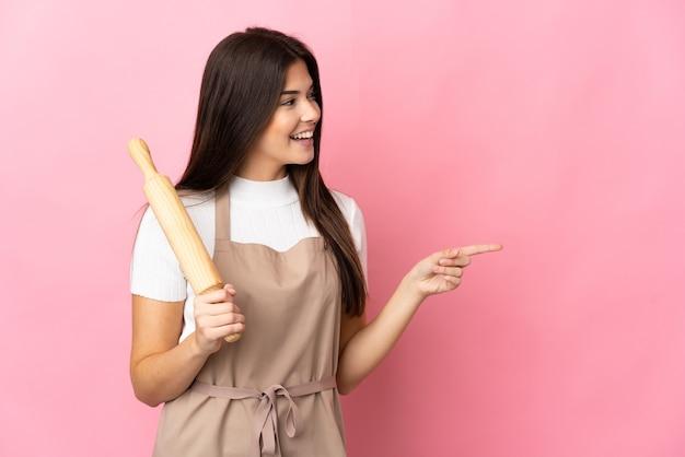 Ragazza brasiliana dell'adolescente che tiene un mattarello isolato sul dito puntato rosa al lato e che presenta un prodotto