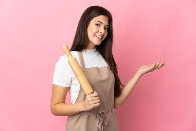Ragazza brasiliana dell'adolescente che tiene un mattarello isolato sulla parete rosa che estende le mani al lato per invitare a venire