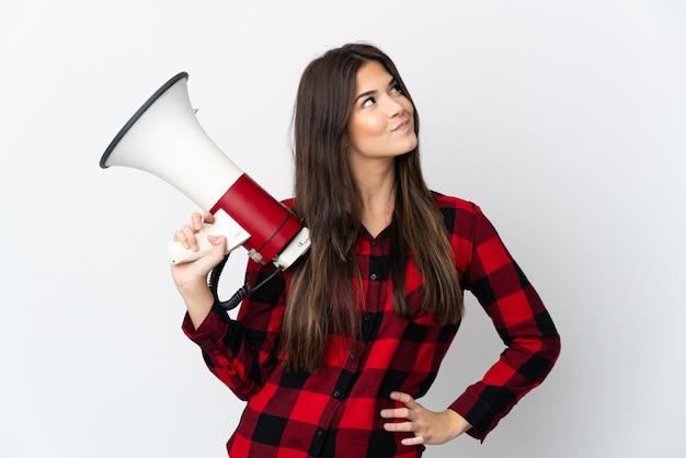 Ragazza brasiliana dell'adolescente isolata sulla parete bianca che tiene un megafono e che pensa