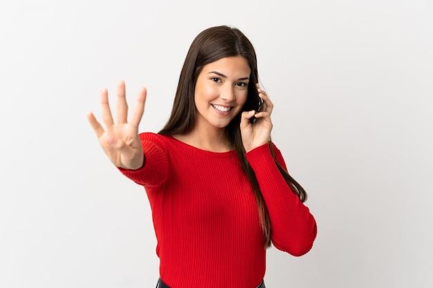 Ragazza brasiliana dell'adolescente che per mezzo del telefono cellulare sopra fondo bianco isolato felice e che conta quattro con le dita