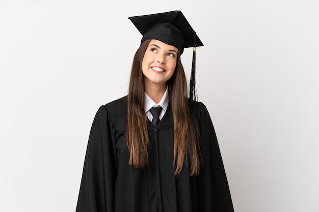 Adolescente laureato brasiliano su sfondo bianco isolato pensando a un'idea mentre guarda in alto