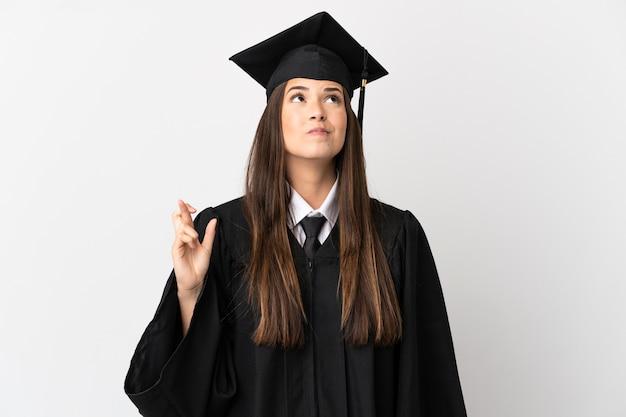 Adolescente laureato universitario brasiliano su sfondo bianco isolato con le dita incrociate e augurando il meglio