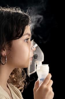 Adolescente che respira la medicina per la tosse attraverso un nebulizzatore