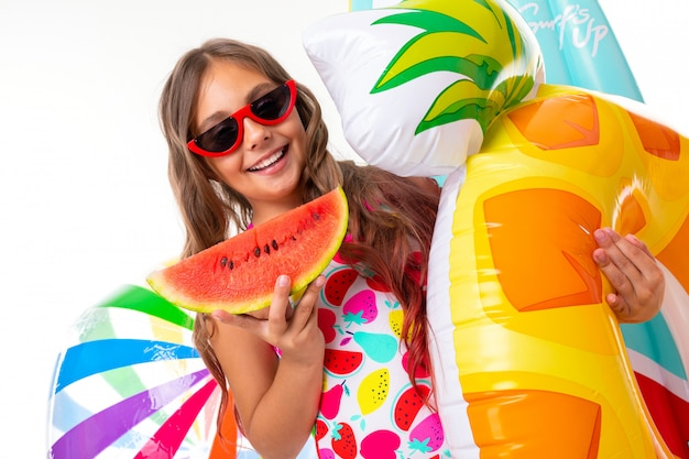 Ragazza caucasica dell'adolescente in occhiali da sole con i materassi di gomma e dell'anguria sulla parete bianca