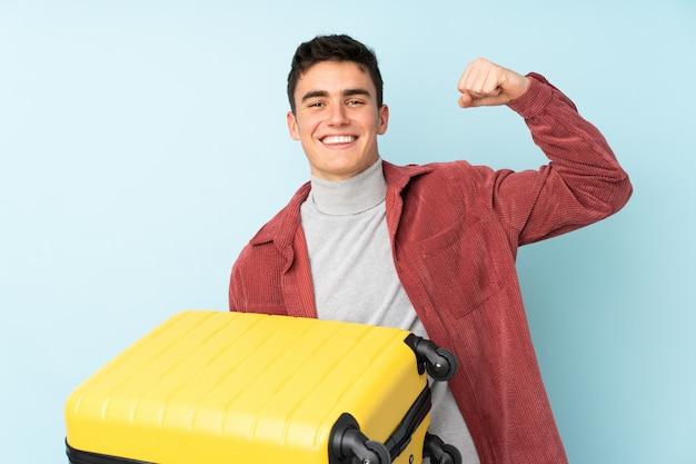 Uomo caucasico dell'adolescente isolato su fondo porpora in vacanza con la valigia di viaggio