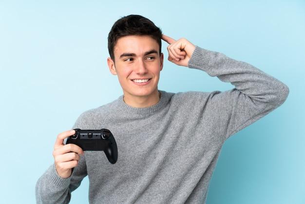 Uomo caucasico dell'adolescente che gioca con un regolatore del videogioco isolato sul blu Foto Premium