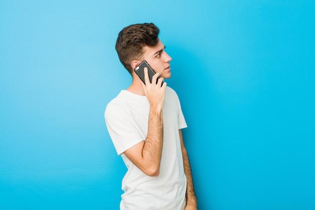 Uomo caucasico dell'adolescente che parla sul telefono