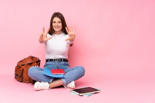 Ragazza caucasica dello studente dell'adolescente che si siede sul pavimento isolato sulla parete rosa che conta otto con le dita
