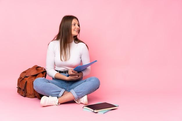 Ragazza caucasica dello studente dell'adolescente che si siede sul pavimento isolato sulla parete rosa felice e sorridente