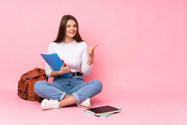 Ragazza caucasica dello studente dell'adolescente che si siede sul pavimento isolato sulla parete rosa che indica il lato per presentare un prodotto