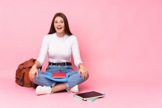 Ragazza caucasica dello studente dell'adolescente che si siede sul pavimento isolato sulla parete rosa con espressione facciale di sorpresa