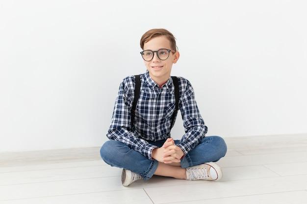 Adolescente, bambini e concetto di moda - bambino carino con gli occhiali seduto sul pavimento sopra il muro bianco