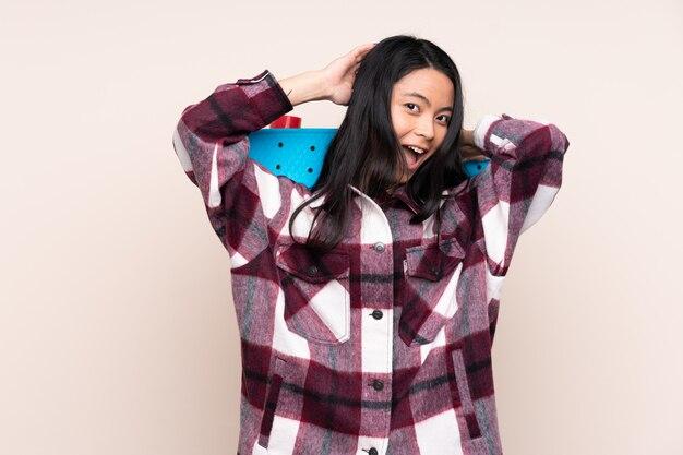 Ragazza cinese dell'adolescente isolata su fondo beige con un pattino e cercare