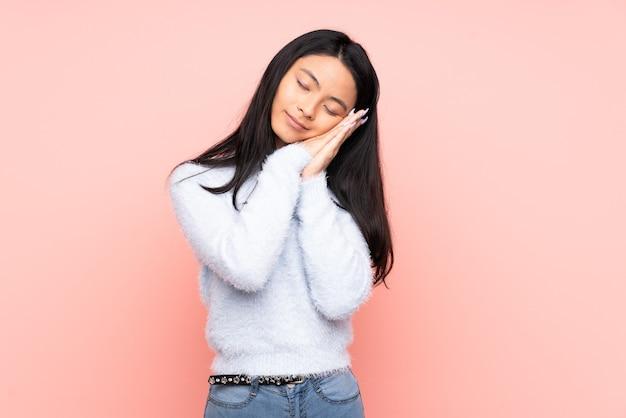 Donna cinese dell'adolescente isolata sulla parete rosa che fa gesto di sonno nell'espressione dorable
