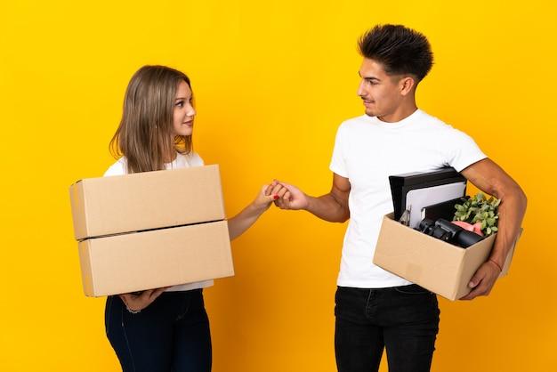 Coppia di adolescenti in movimento nella nuova casa tra scatole su handshake blu dopo un buon affare