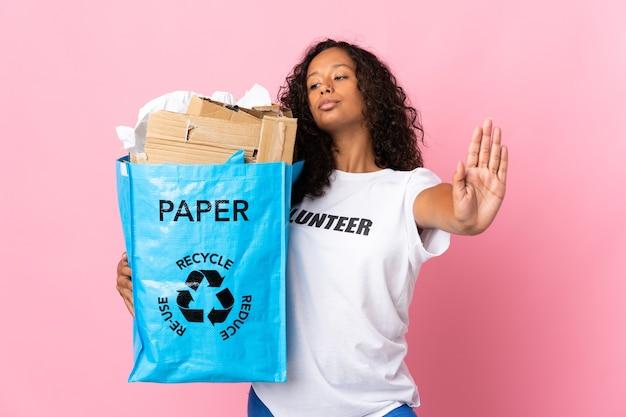 Ragazza cubana dell'adolescente che tiene un sacchetto di riciclaggio pieno di carta da riciclare isolato su fondo rosa che fa gesto di arresto e deluso