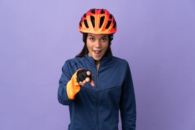 Ragazza del ciclista dell'adolescente sorpresa e che indica la parte anteriore