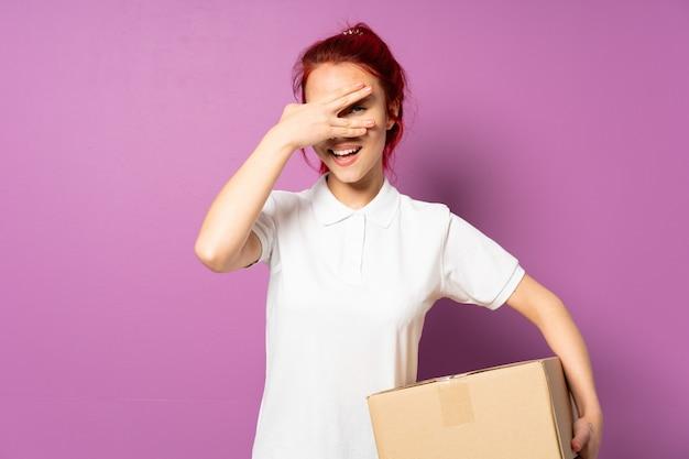 La ragazza della consegna dell'adolescente sul rivestimento viola della parete osserva a mano e sorridendo