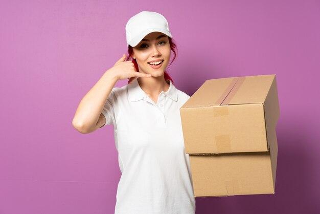 Donna di consegna dell'adolescente isolata sulla parete viola che fa gesto del telefono e che indica parte anteriore