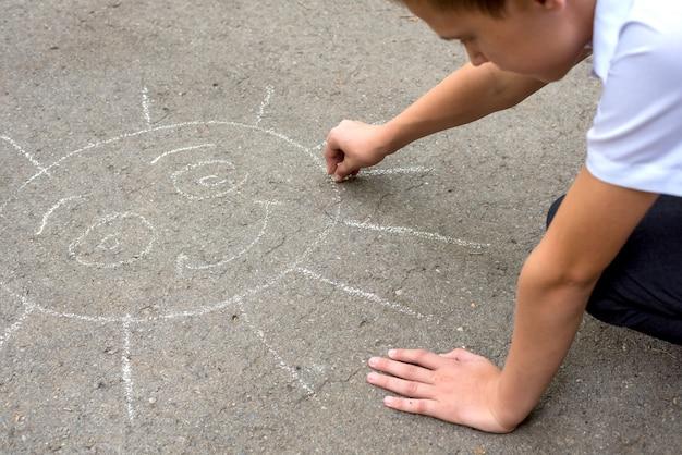 L'adolescente disegna il sole sul marciapiede con il gesso. messa a fuoco selettiva. adolescente in una camicia bianca.