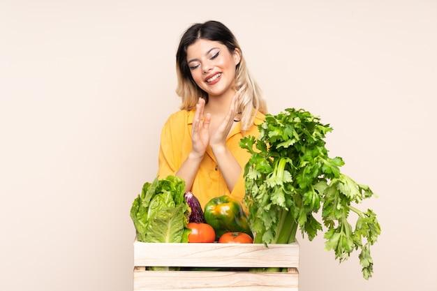 Ragazza del coltivatore dell'adolescente con le verdure appena raccolte in una scatola