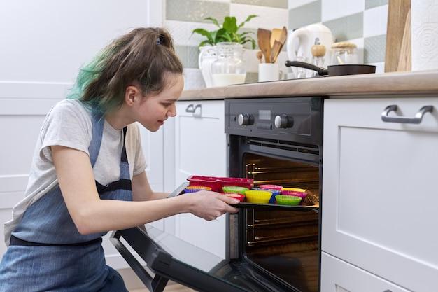 Ragazza adolescente in un grembiule con la preparazione di cupcakes crudi in stampi in silicone, mettendo il vassoio in forno, sfondo interno della cucina casalinga. hobby per adolescenti, cucina casalinga, cibo sano fatto in casa