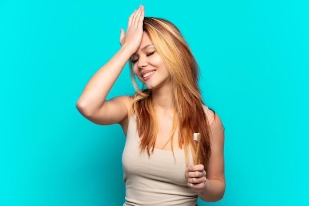 La ragazza dell'adolescente che si lava i denti su uno sfondo blu isolato ha realizzato qualcosa e intendeva la soluzione