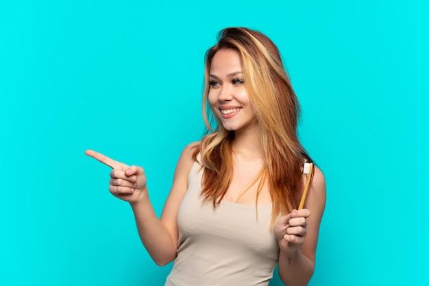 Ragazza adolescente lavarsi i denti su sfondo blu isolato puntare il dito di lato e presentare un prodotto