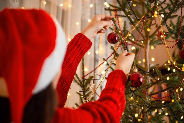 Ragazza dell'adolescente che decora l'albero di natale alla vigilia di capodanno