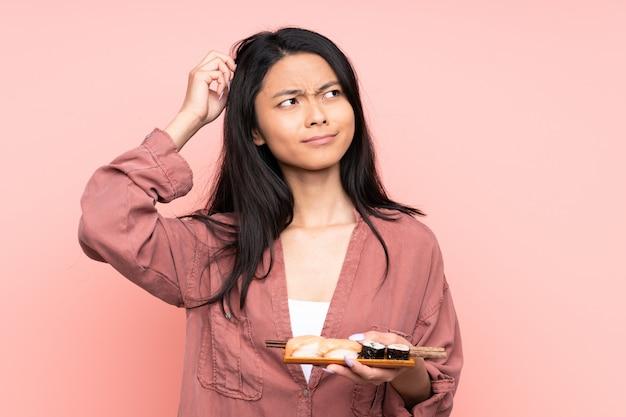 Ragazza dell'adolescente che mangia i sushi isolati sul rosa che ha dubbi e con l'espressione confusa del fronte