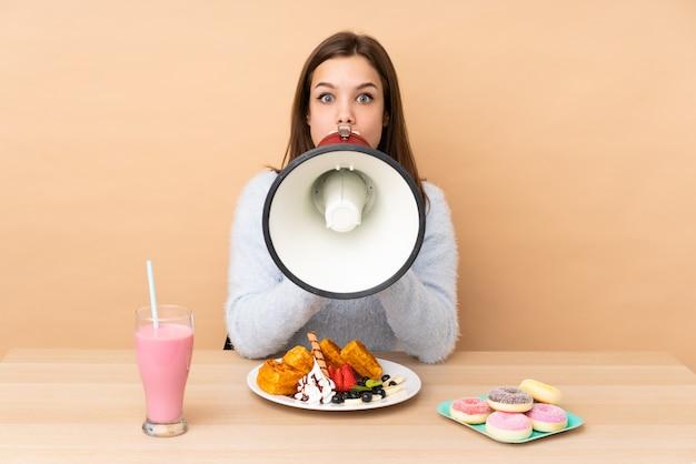 Ragazza dell'adolescente che mangia le cialde sulla parete beige che grida tramite un megafono