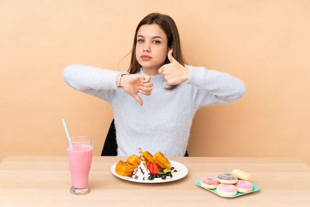 Ragazza dell'adolescente che mangia le cialde isolate sulla parete beige che fa segno buono-cattivo. indeciso tra sì o no