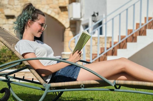 Ragazza adolescente con gli occhiali che legge un libro, che riposa sul lettino in piedi in cortile adolescenti, svago, estate, conoscenza