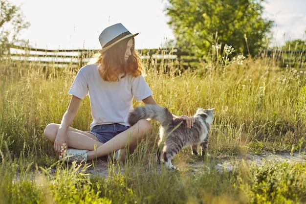 Ragazza dell'adolescente in cappello sulla natura che gioca con il gatto lanuginoso grigio, campagna