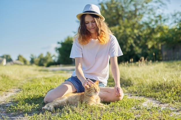 Ragazza dell'adolescente in cappello sulla natura che gioca con il gatto rosso, stile rustico