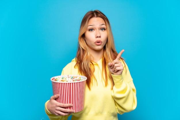 Ragazza dell'adolescente che tiene i popcorn sopra fondo blu isolato che intende realizzare la soluzione mentre solleva un dito