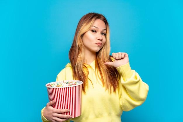 Ragazza dell'adolescente che tiene i popcorn sopra fondo blu isolato orgoglioso e soddisfatto di sé