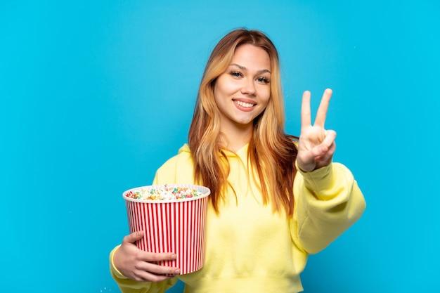 Ragazza dell'adolescente che tiene i popcorn sopra fondo blu isolato che sorride e che mostra il segno di vittoria