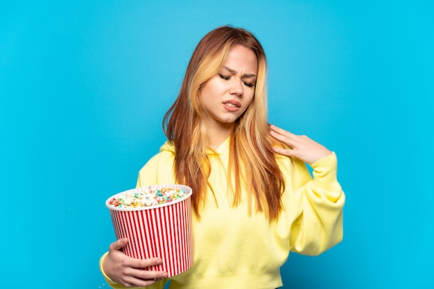 Ragazza dell'adolescente che tiene i popcorn sopra fondo blu isolato che soffre di dolore alla spalla per aver fatto uno sforzo