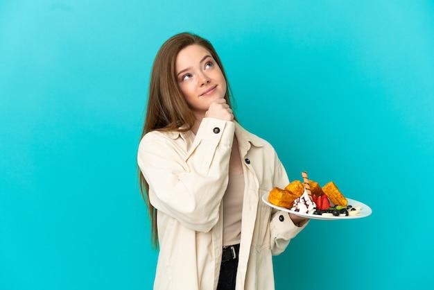 Ragazza adolescente con waffle su sfondo blu isolato e guardando in alto