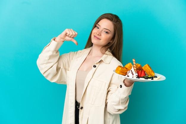 Ragazza adolescente con waffle su sfondo blu isolato orgoglioso e soddisfatto di sé