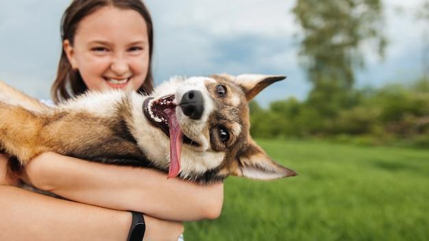 La ragazza adolescente abbraccia un cane e guardano la telecamera